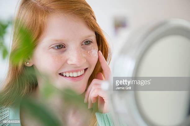 Girl (12-13) applying moisturizer, Jersey City, New Jersey, USA