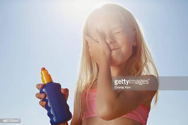 Girl applying sunblock on face