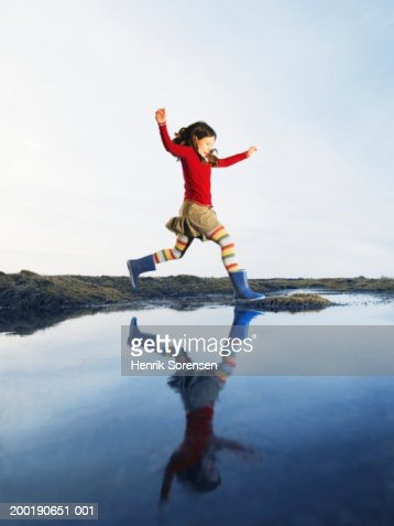 Girl (8-10) arms raised, leaping over water onto grassy mound