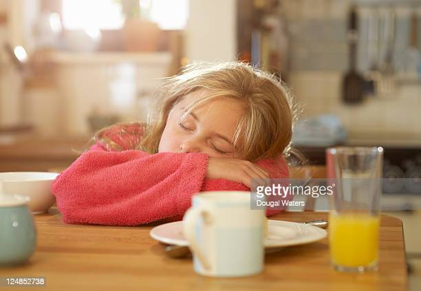 Girl asleep at kitchen breakfast table.