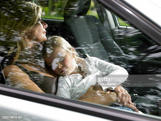 Girl (4-6) asleep in mothers lap in car (blurred motion)