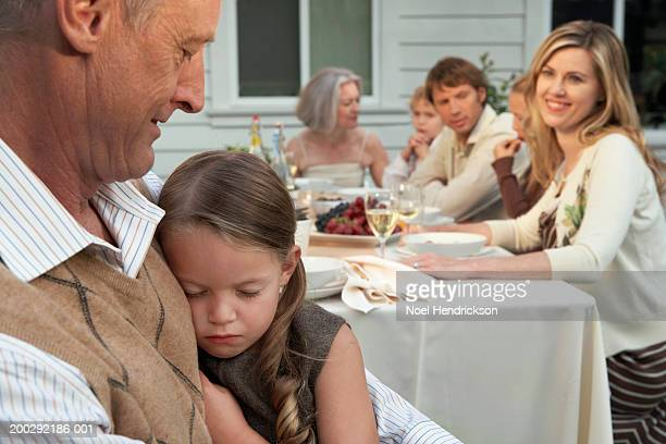 Girl (5-7 years) asleep on grandfather's lap by dining table outdoors, mother watching in background
