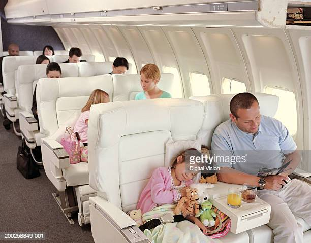 Girl (5-7) asleep on plane surrounded by soft toys, next to father