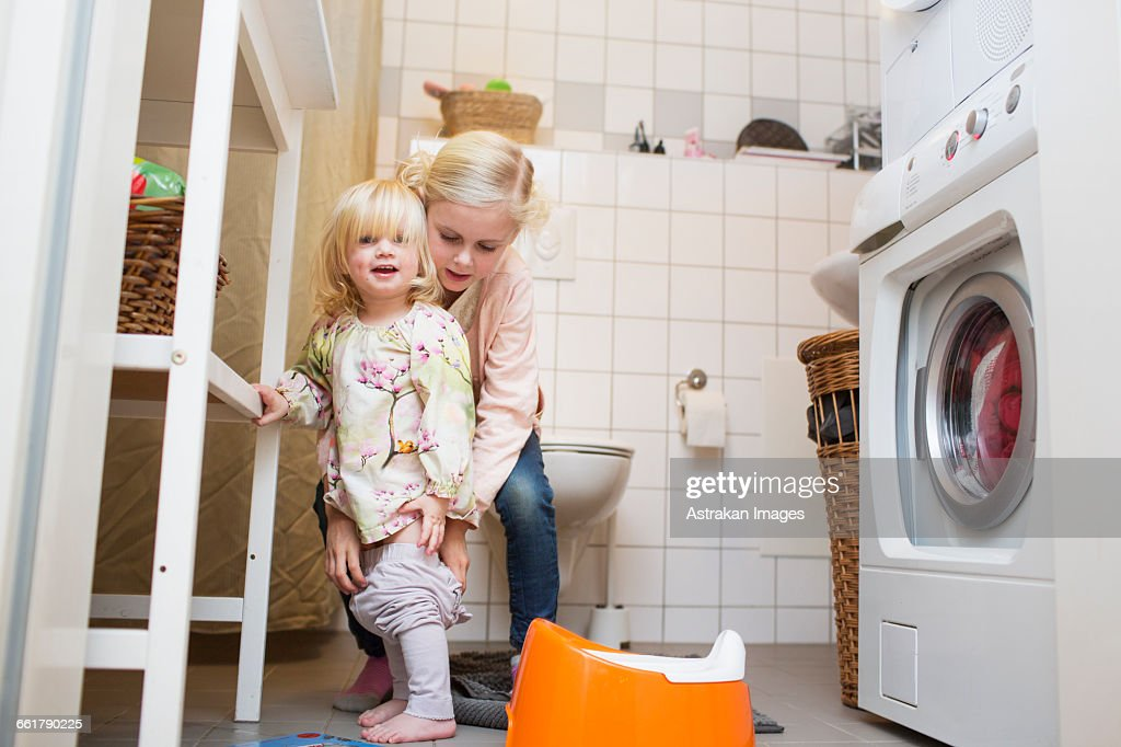 Girl assisting sister to wear pants at bathroom stock for Bathroom wear