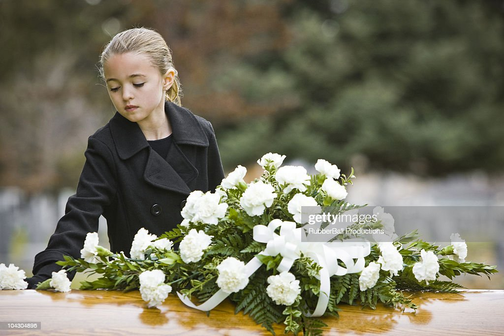 girl at a funeral standing next to a coffin