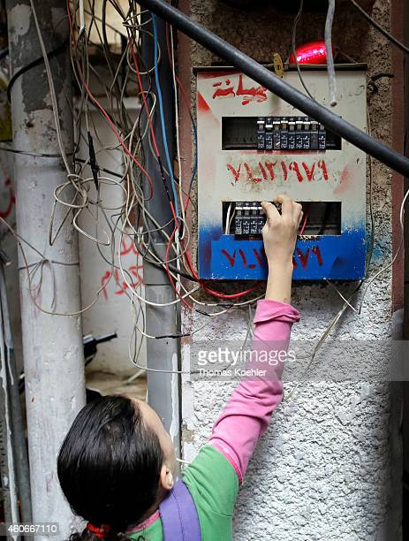 Girl at a fuse box in the Palestinian refugee camp Bourj elBarajneh on December 09 2014 in Beirut Lebanon Repeatedly there are cases of death by...