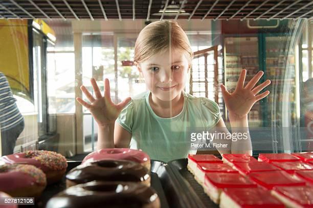 Girl (6-7) at bakery looking through cabinet at doughnuts