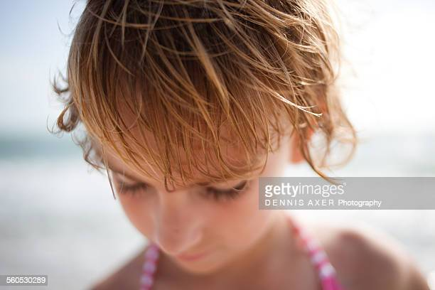 Girl at beach looking down and playing