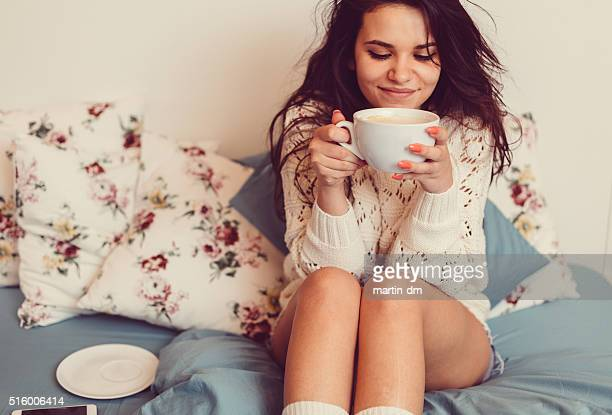 Girl at bed drinking coffee