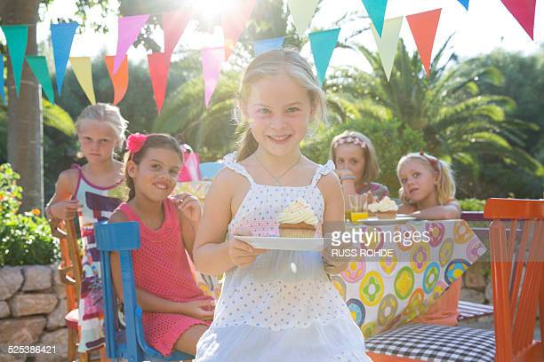 Girl at birthday party holding plate with cupcake