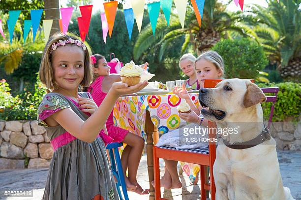 Girl at birthday party with dog holding cupcake