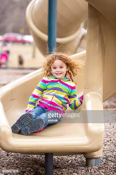 Girl At Bottom of Twisted Slide on Playground