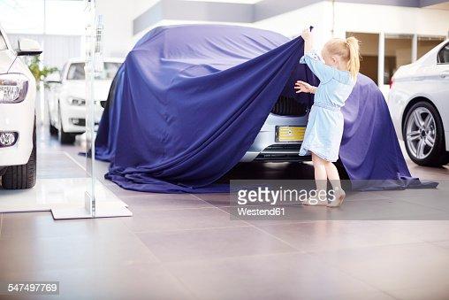 Girl at car dealer unveiling tarpaulin