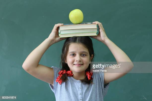 Girl at classroom holding a stack of books and an apple on her head.