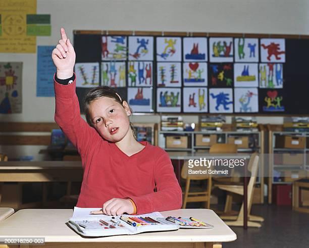 Girl (8-10) at desk raising hand in classroom, portrait