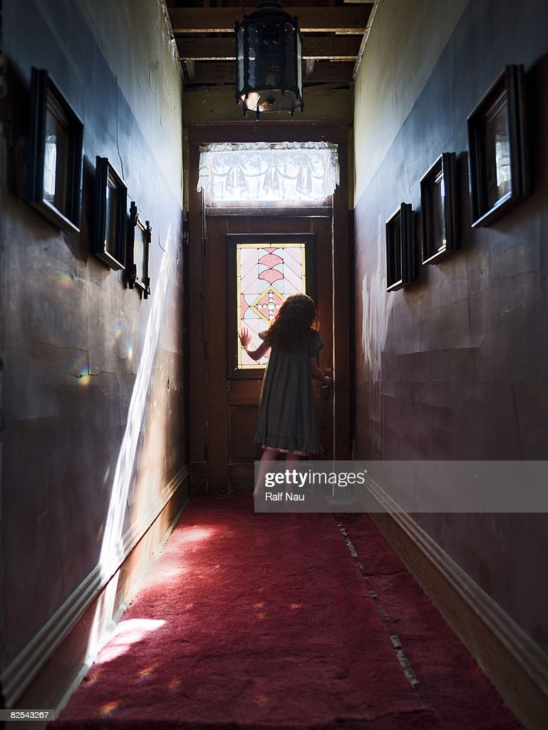 Girl at door with sunlight streaming through : Stock Photo