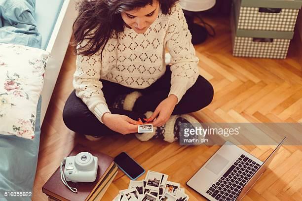 Menina em casa a desfrutar de fotografias instantâneas