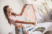 Beautiful girl in casual clothes is holding a new blouse, looking at it and smiling while resting in her room at home