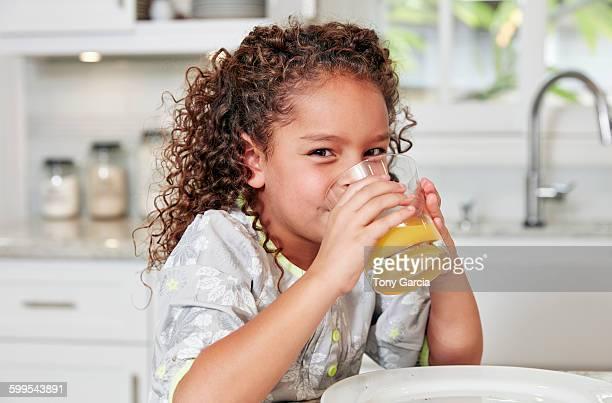 Girl at kitchen counter drinking orange juice looking at camera