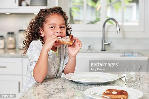 Girl at kitchen counter eating toast looking at camera