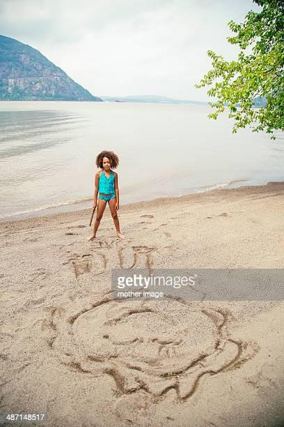 Girl at lake drawing in sand
