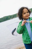 Girl at lake holding fish in net