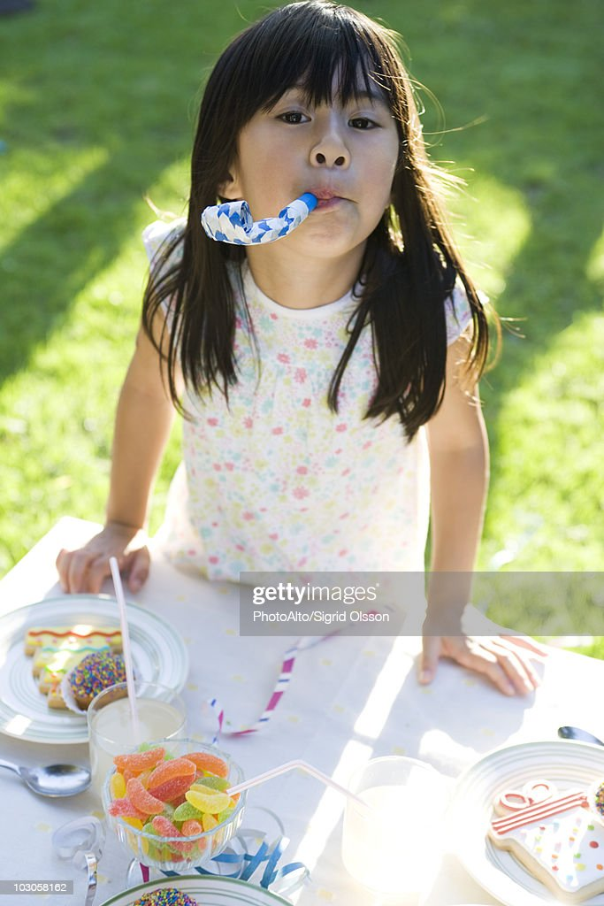 Girl at party enthusiastically blowing party horn blower