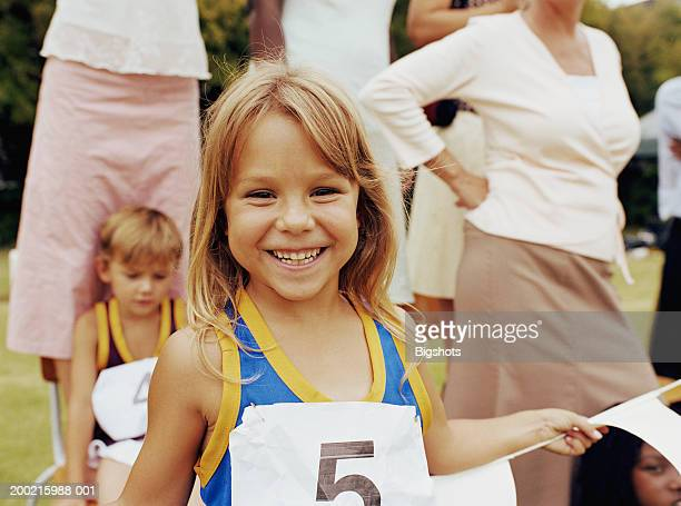 Girl (5-7) at school sports day, smiling, portrait
