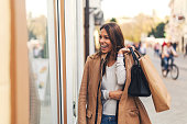 Woman with shopping bags in front on store window