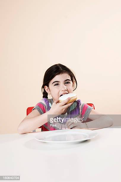 Girl at table eating a donut