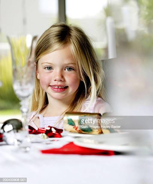Girl (3-5) at table set for Christmas dinner, smiling, portrait