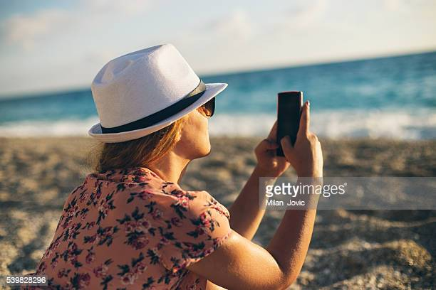 Girl at the beach texting on smartphone