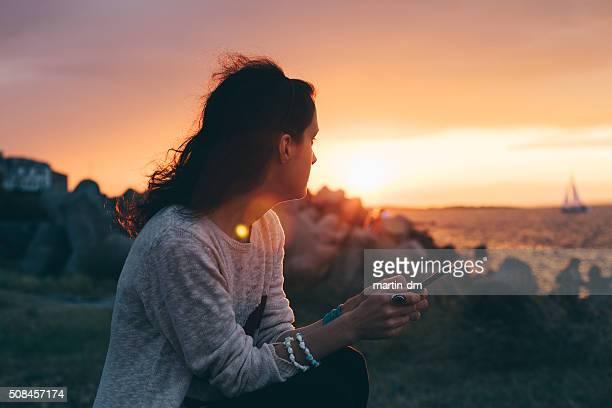 Fille sur la plage au coucher du soleil à envoyer des SMS