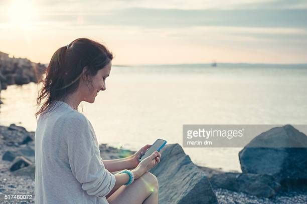 Girl at the beach using smartphone