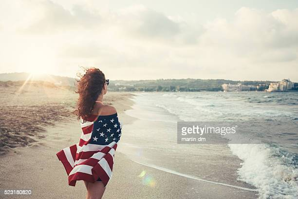 Ragazza alla spiaggia avvolto nella bandiera Stati Uniti d'America