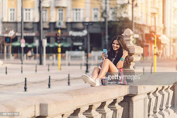 Girl at the bridge texting on smartphone