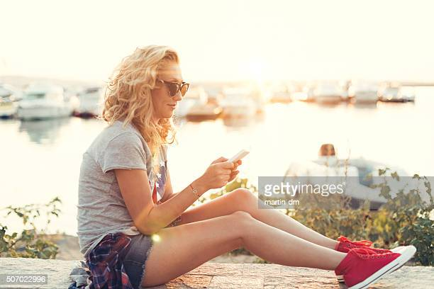 Girl at the port yacht texting