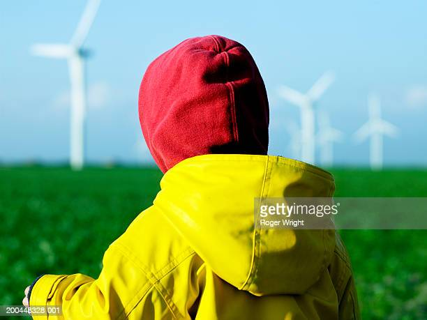 Girl (2-4) at wind farm, close-up, rear view