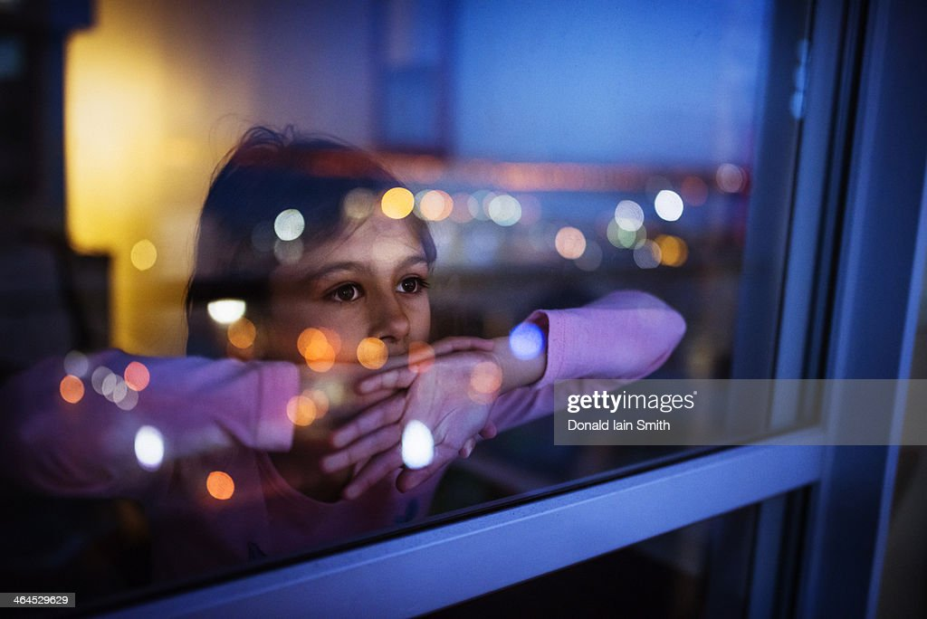 Girl at window with reflected city lights