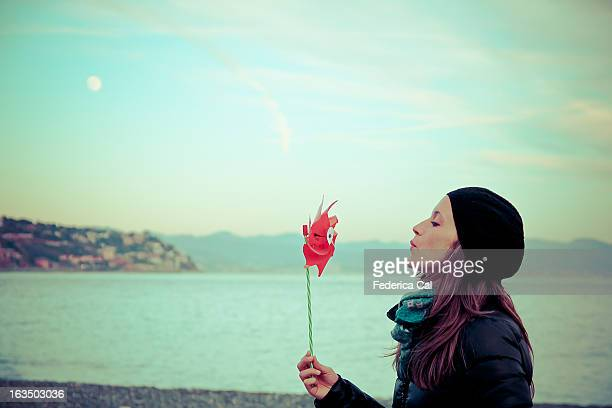 Girl at winter seaside, blowing red pinwheel