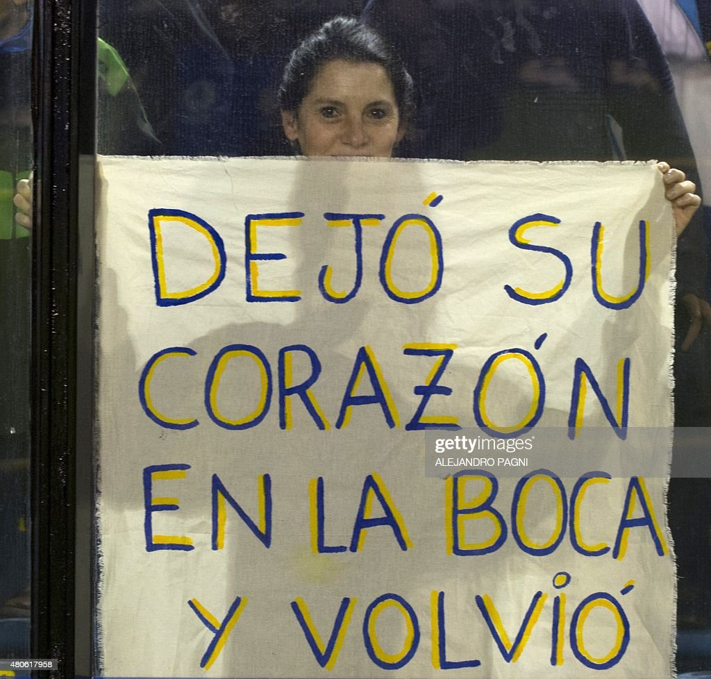 A girl attending Boca Juniors's newly returned player Carlos Tevez's official presentation holds a placard that reads 'He left his heart in the Boca (the neighborhood) and came back home', at La Bombonera stadium in Buenos Aires, on July 13, 2015.