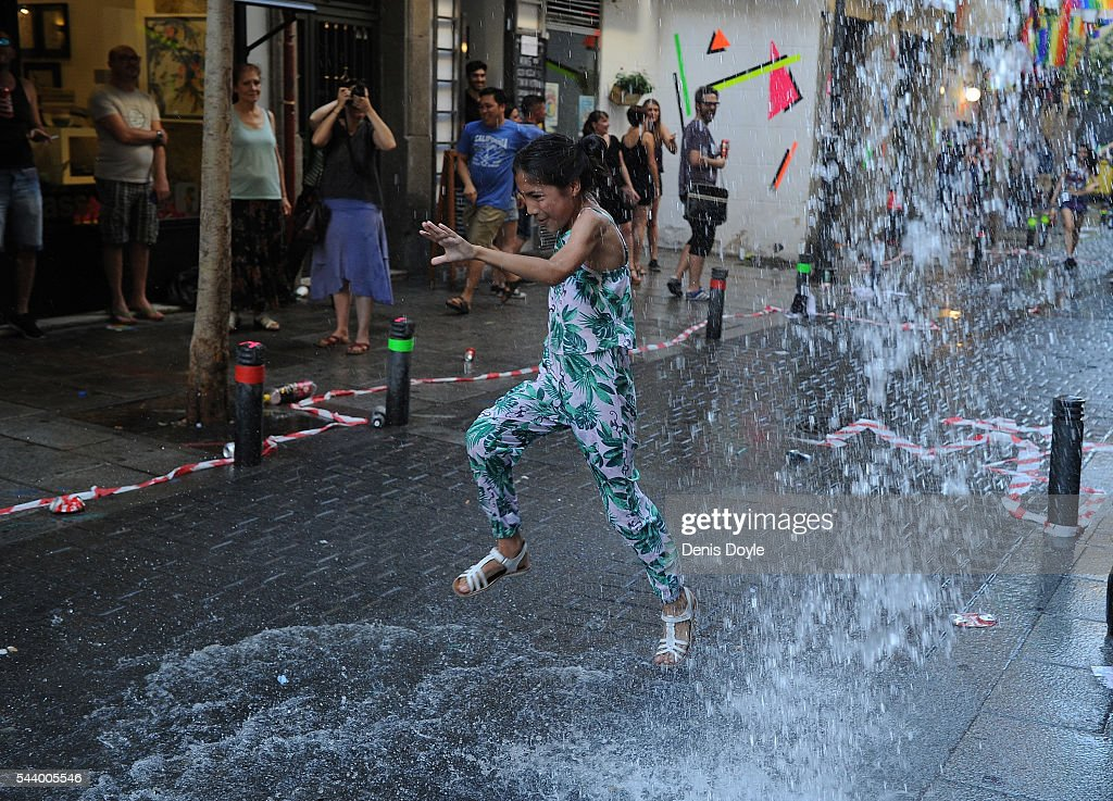 A girl avoids water thrown from a balcony during the 2016 Madrid Gay Pride week on June 30, 2016 in Madrid, Spain. Hundreds of thousands of revellers celebrate the Gay Pride week in Madrid, one of the biggest in Europe.