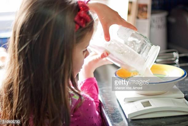 Girl baking at home, measuring ingredients
