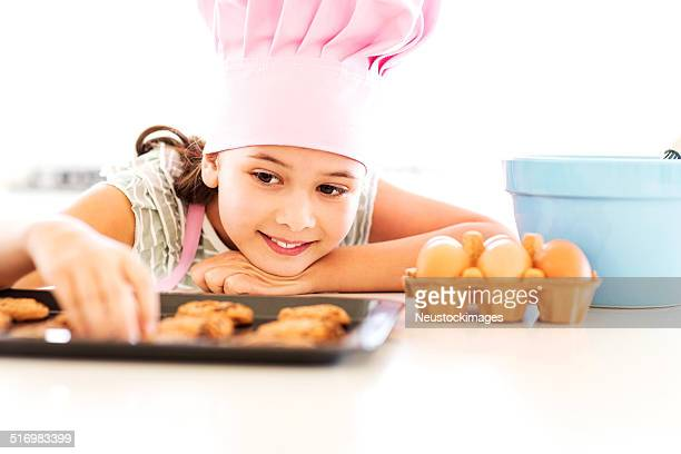 Girl Baking Cookies While Resting At Counter Top