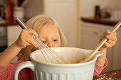 Girl (4-5) baking in kitchen, close-up