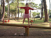 Girl (10-12) balancing atop seesaw, arms outstretched