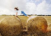 Girl balancing between two bales of hay