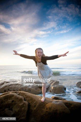 girl balancing on a seaside boulder : Stock Photo