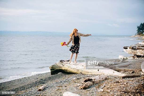 Girl balancing on driftwood on beach