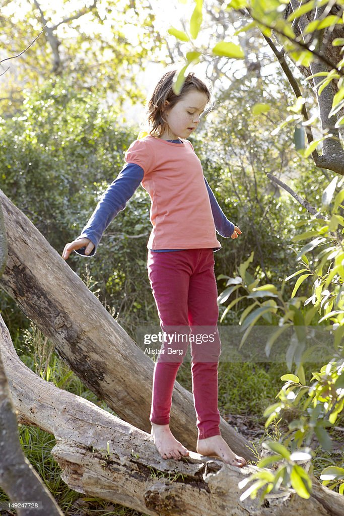 Girl balancing on log in forest : Stock Photo